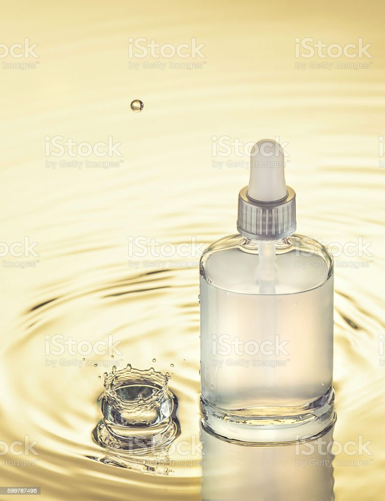 Moisturizing serum on the yellow water background stock photo