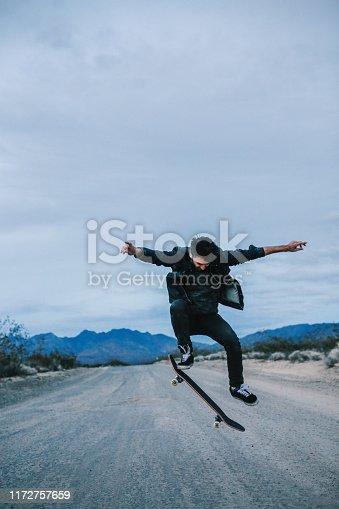 Young man doing skateboard tricks on the gravel road in Mojave desert