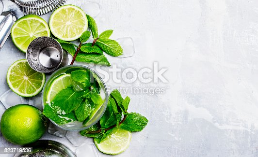 istock Mojito alcoholic cocktail and bar tools, drink background, vintage toned image, top view 823719536