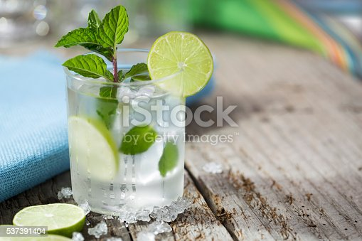 A mojito at the beach with lime and fresh mint with crushed ice on a rustic wood table with the ocean in the background.  Please see my portfolio for other food and drink images.