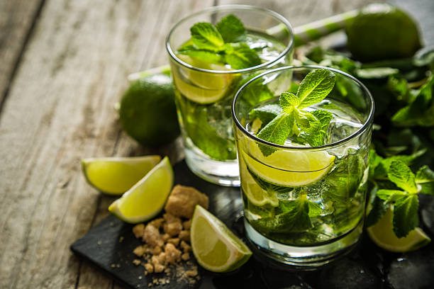 Mojito cocktail and ingredients Mojito cocktail and ingredients, rustic wood background, copy space mojito stock pictures, royalty-free photos & images