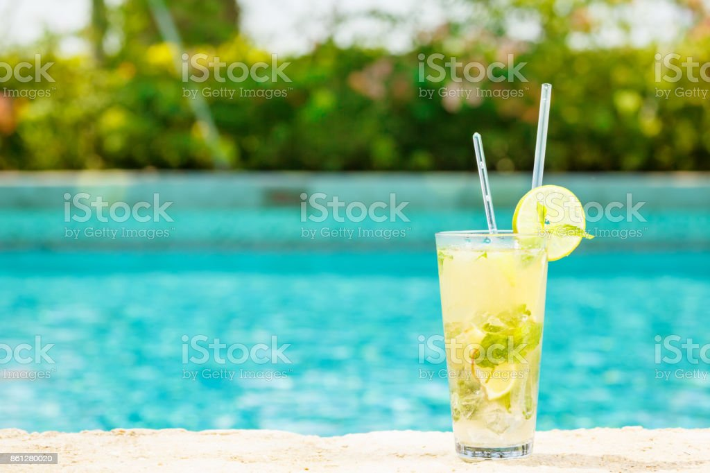 Mojito cocktail at the edge of a resort pool.  Concept of luxury vacation stock photo