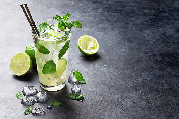 Mojito cocktail Mojito cocktail on dark stone table. With space for your text mojito stock pictures, royalty-free photos & images