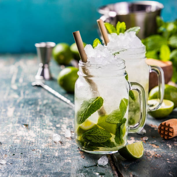Mojito cocktail Mojito cocktail with lime and mint in glass jars on the table. Copy space mojito stock pictures, royalty-free photos & images