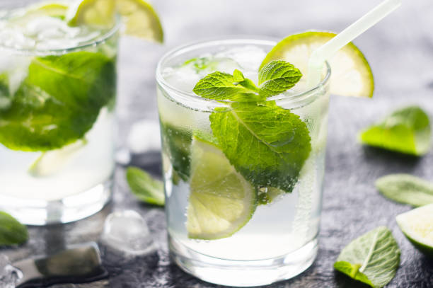 Mojito cocktail. Mojito cocktail with lime and mint in glass at sunlight. Closeup photo. mojito stock pictures, royalty-free photos & images