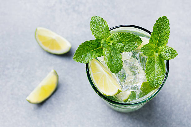 Mojito cocktail with lime and mint in highball glass Mojito cocktail with lime and mint in highball glass on a grey stone background Top view Copy space mojito stock pictures, royalty-free photos & images
