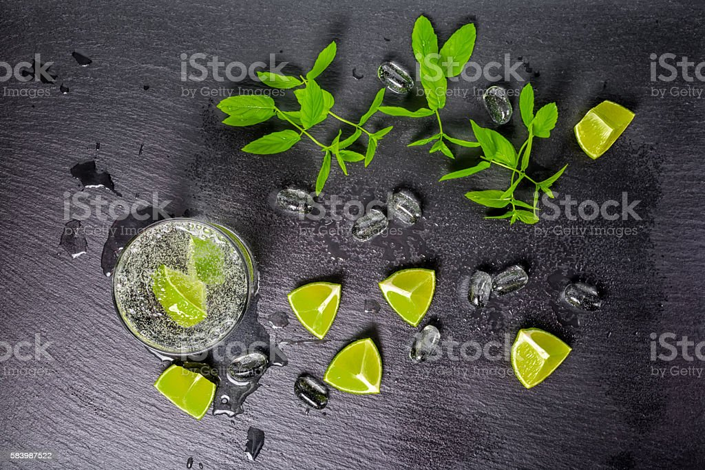 mojito cocktail with splash, ice, green mint, cuted limes stock photo