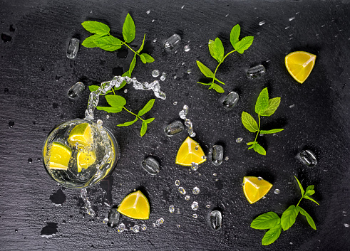 mojito cocktail with splash, ice, green mint, limes and drops