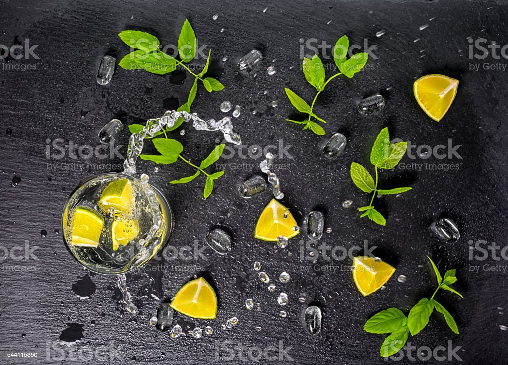 mojito cocktail with splash, ice, green mint, limes and drops stock photo