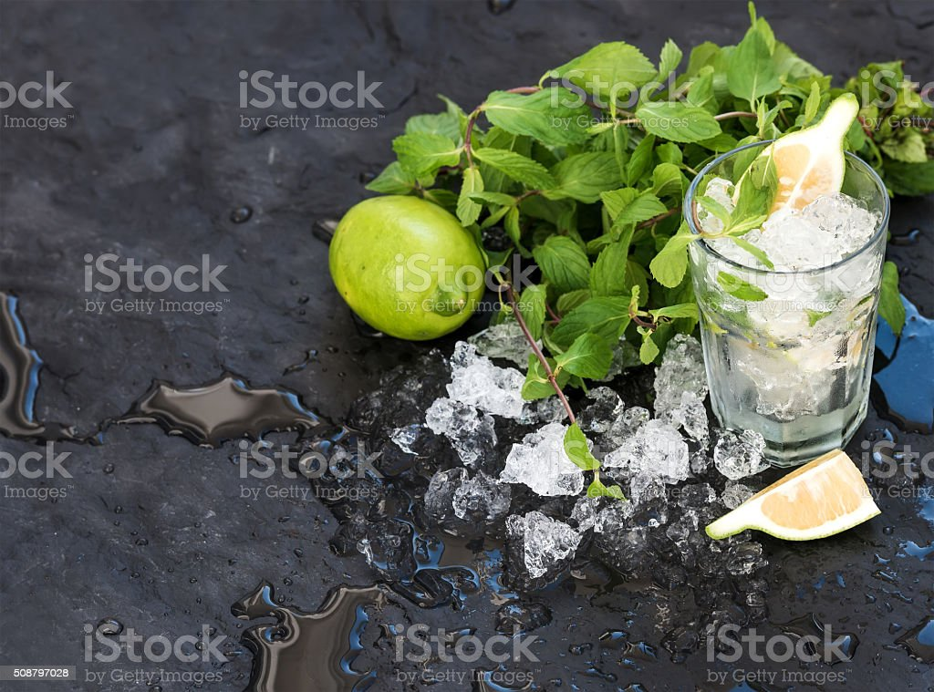 Mojito cooking set. Bunch of fresh mint, lime, chipped ice stock photo