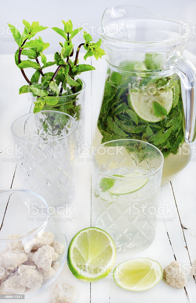 Mojito in the glass and jug, lime, cane sugar, mint stock photo
