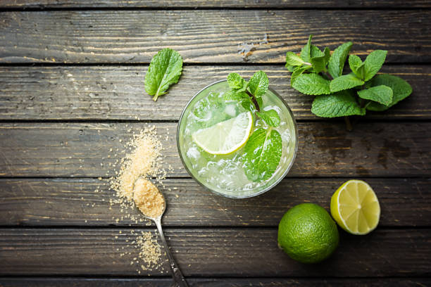 Mojito shot from birds eye view Refreshing mint cocktail mojito with rum and lime, cold drink or beverage with ice on white wooden background, top view mojito stock pictures, royalty-free photos & images