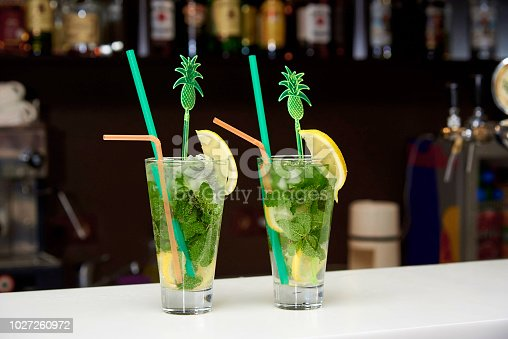 Mojito with ice and bright straws on the bar.