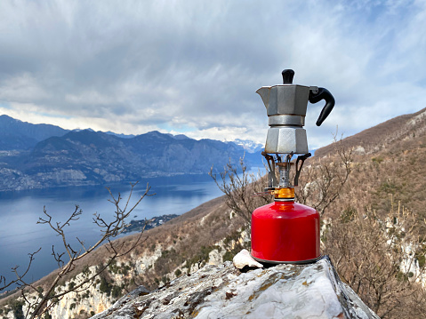 Moka coffee on portable camping stove with mountains panorama