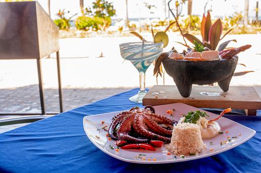 A Molcajete Bowl Filled With Shrimp, Chorizo, Sausage, Pulpo, Mozzarella Cheese, Nopalitos In An Enchilada Sauce