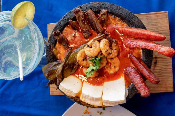 a molcajete bowl gefüllt mit shrimp, chorizo, wurst, pulpo, mozzarella käse, nopalitos in einer enchilada sauce - meeresfrüchte enchiladas stock-fotos und bilder