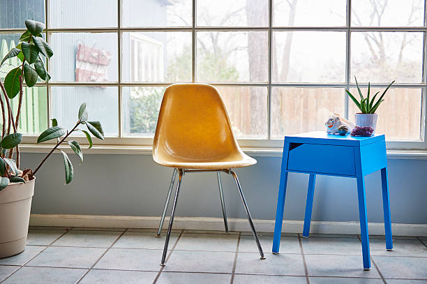 A molded plastic chair and blue side table by a window stock photo