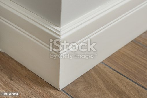 Molding in the interior, baseboard corner. Light matte wall with tiles immitating hardwood flooring.