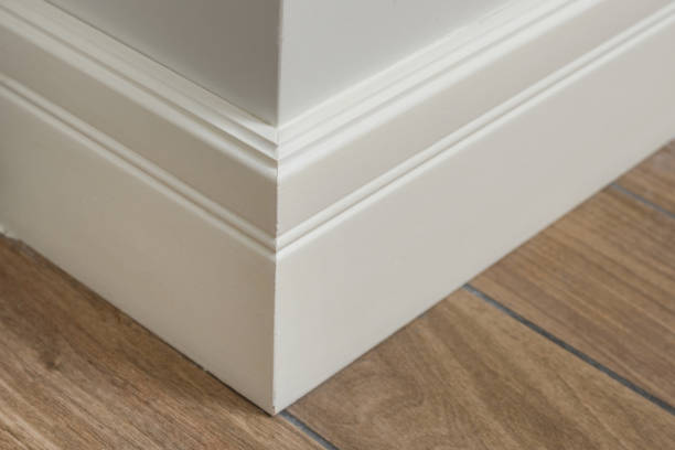 molding in the interior, baseboard corner. light matte wall with tiles immitating hardwood flooring - sztukateria zdjęcia i obrazy z banku zdjęć