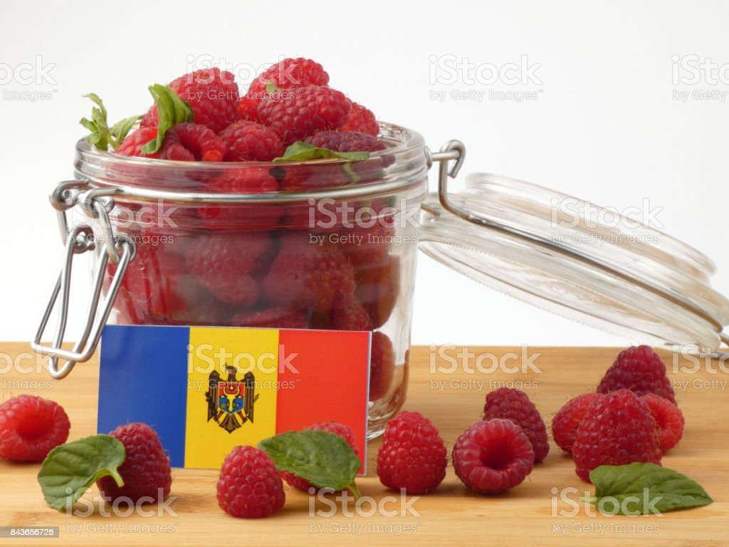 Moldovan flag on a wooden panel with raspberries isolated on a white background stock photo
