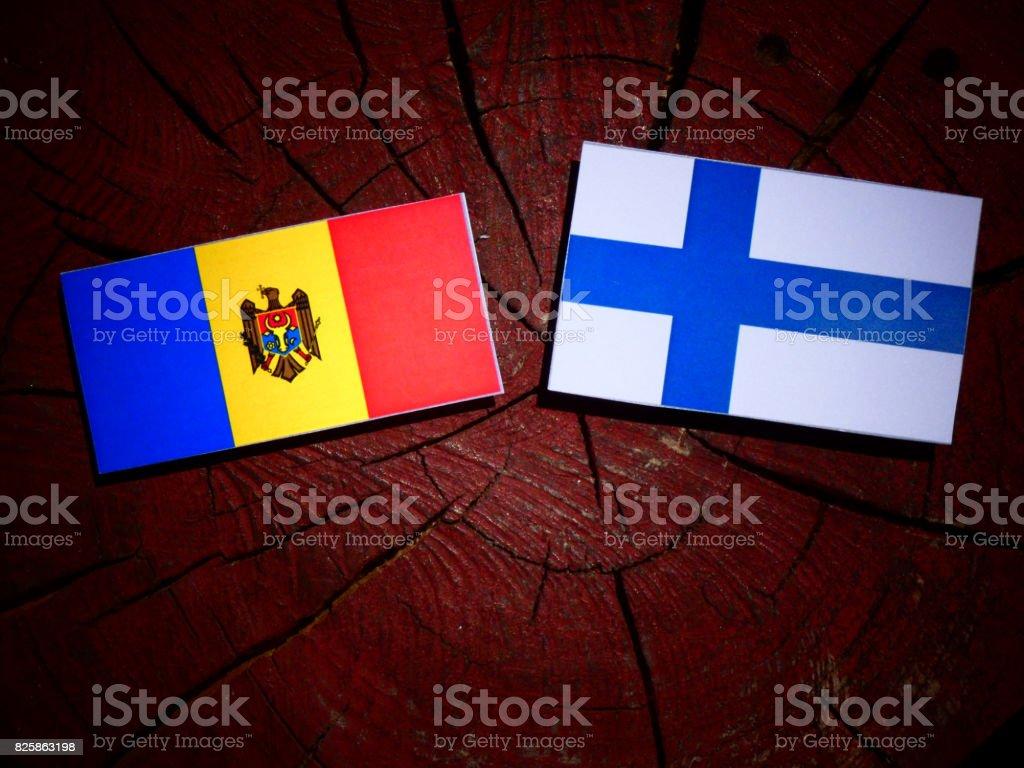 Moldovan flag with Finnish flag on a tree stump isolated stock photo