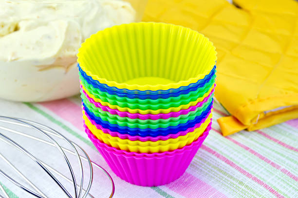 Molds for cupcakes with potholder mixer on fabric stock photo