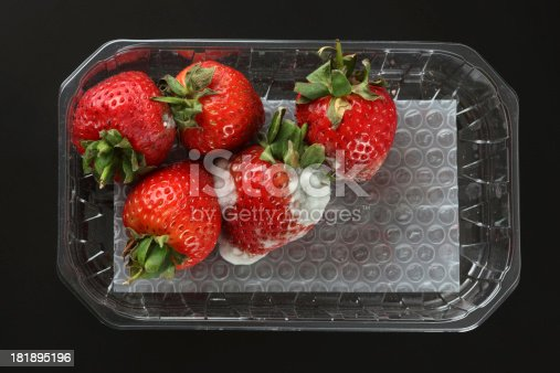 Moldy strawberries in a plastic package. Black background.