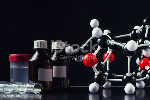 istock molecular formula and laboratory equipment on a dark background close up. Science organic chemistry concept 1072052194