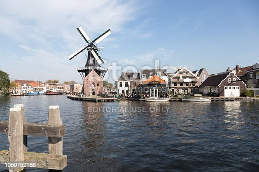 'Haarlem, Netherlands, October 6th 2018: Windmill Adriaan and tourists on waterfront cafe alongside the Spaarne river in Haarlem, Holland, Netherlands