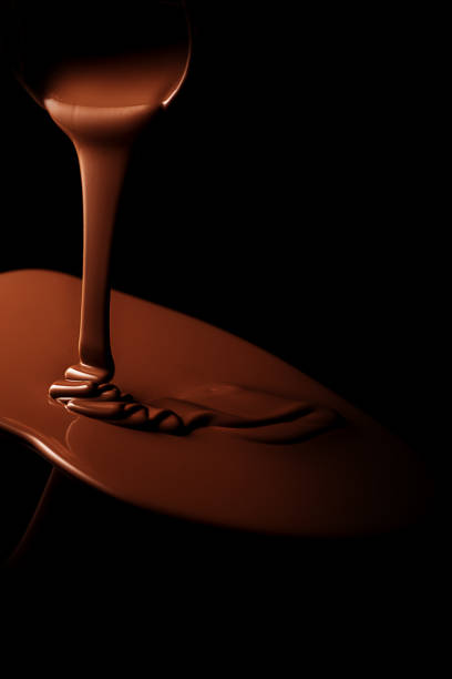 黒い背景とチョコレートの流れと溶融チョコレート - チョコレート ストックフォトと画像
