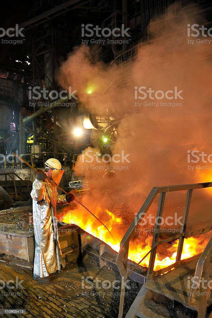 Molten hot steel pouring and worker royalty-free stock photo