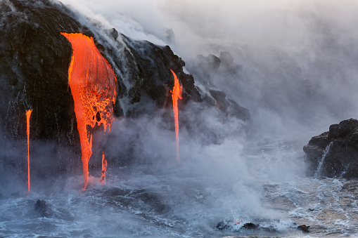 Molten Lava Dripping Into The Ocean Stock Photo - Download Image Now