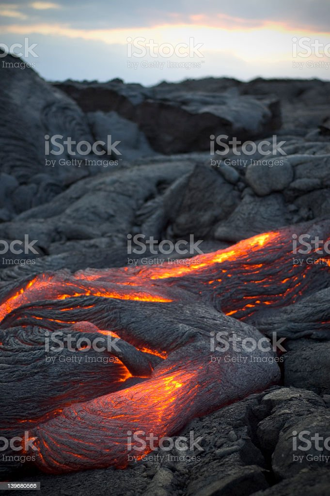 Molten lava flowing surrounded by cooled lava rock Flowing lava on Kona, the big island of Hawaii. Active Volcano Stock Photo