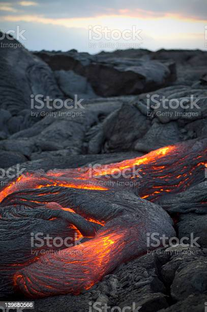 Molten Lava Flowing Surrounded By Cooled Lava Rock Stock Photo - Download Image Now