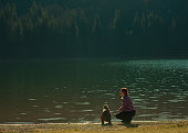 Rear view of redhead mother and baby daughter at the lake, admiring the view, exploring nature