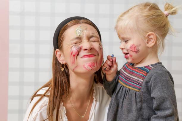 Mama und Baby spielen mit Gesichtsfarbe, Familienzeitkonzept – Foto