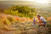 Young beautiful mother with her son walking at sunset in a field in a meadow.