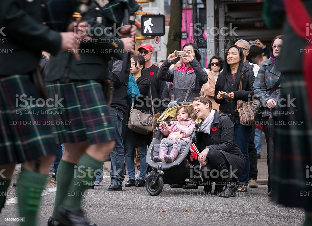 Mom and baby watch the Remembrance Day parade stock photo