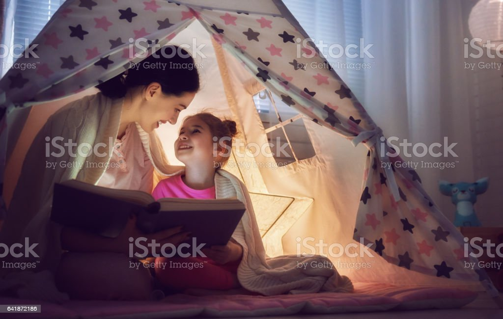 Mom and child are reading book stock photo