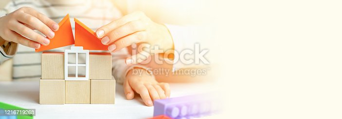 657779378 istock photo Mom and child build a house of wooden cubes and blocks constructor. Close up of hands holding roof elements. Playing parents and children at home. Credit, real estate and mortgage financial concept. 1216719268