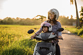 mom and child enjoy riding motorcycle scooter togehter