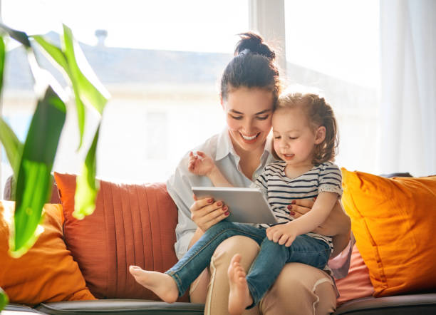 mom and child with tablet stock photo