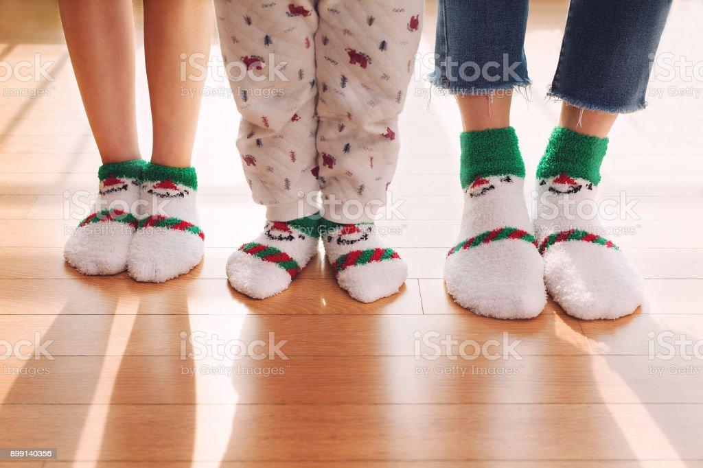 Anne ve çocuk oturma odasında şirin çorap ile ayakta duruyorlar. Bacaklarını kapat stok fotoğrafı