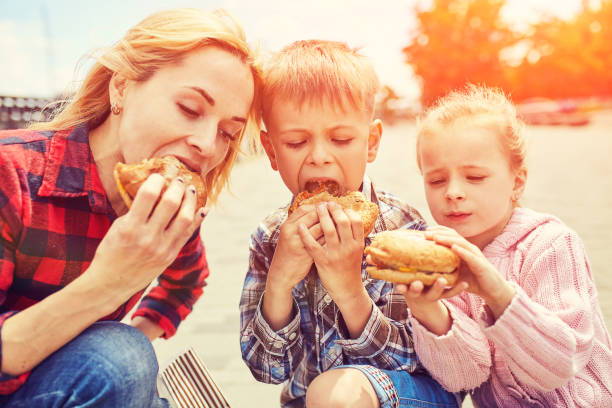 Mom and children eating a hamburger outdoors stock photo