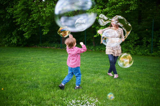 Mom and children playing soap bubbles on the green lawn in the park. stock photo