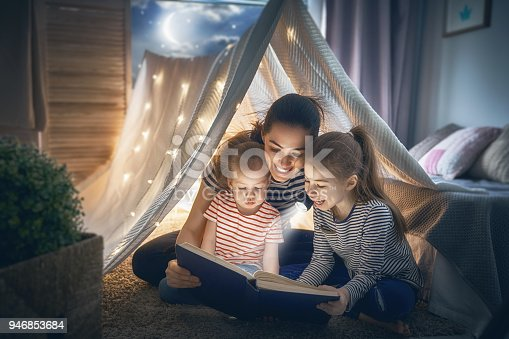 istock Mom and children reading book 946853684