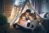 Family bedtime. Mom and children daughters are reading a book in tent. Pretty young mother and lovely girls having fun in children room.