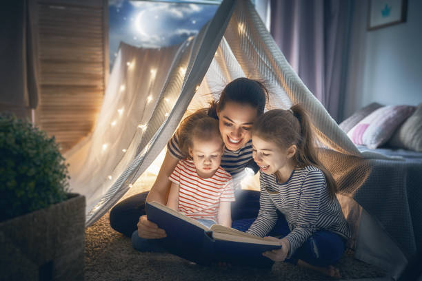 Mom and children reading book Family bedtime. Mom and children daughters are reading a book in tent. Pretty young mother and lovely girls having fun in children room. tent stock pictures, royalty-free photos & images