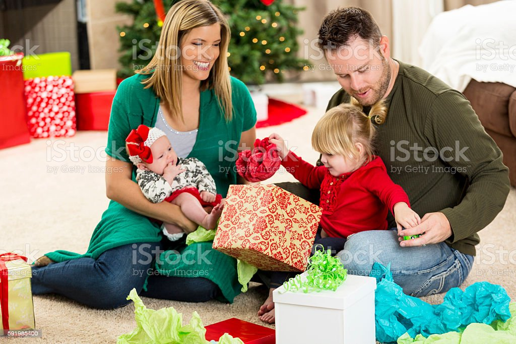 mom and dad open gifts with young daughters at christmastime royalty free stock photo