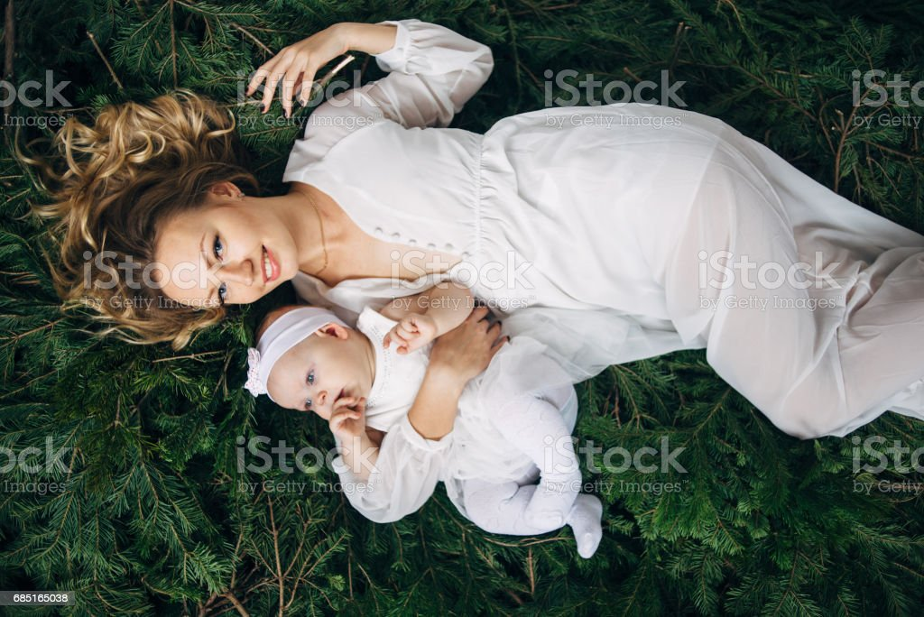 Mom and daughter are lying on Christmas trees foto de stock royalty-free